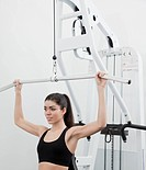 Hispanic woman using weight machine in health club