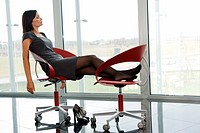 Professional woman resting her legs up on office chair (thumbnail)