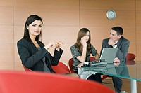 Professional woman in office with couple at laptop