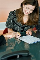 Young woman signing document, female hand pointing