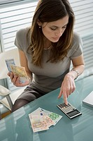 Professional woman adding up euro bills with calculator (thumbnail)