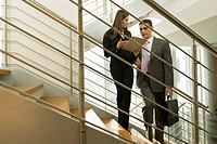 Businessman and businesswoman on staircase discussing over document