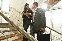 Businessman and businesswoman on staircase arguing over document