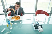 Businessman eating pizza at desk