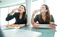 Businesswomen eating pizza at desk