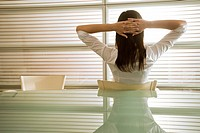 Back view of businesswoman in office with hands behind head