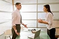 Businessman in office talking to businesswoman