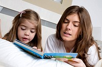 Young woman and girl on bed reading a book