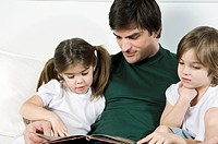 Young man on couch with children reading