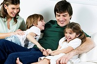 Young couple on couch with children laughing