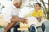 Grandfather pushing boy in soapbox car
