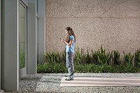 Businesswoman using cell phone in front of building