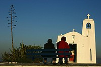 Old women sitting in front of Church Agios Nikolaos near the port of Rafina, located on the eastern coast of Attica, Greece, Europe