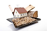Wood pellets on Dustpan, toy house and logs, close_up