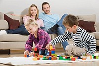 Family at home, children playing with building bricks