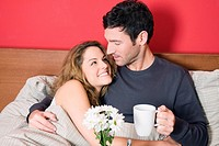Young couple having breakfast in bed