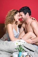 Young couple embracing in bed, smiling