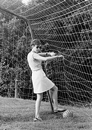 Sixties, black and white photo, people, young girl stands in a football goal and picks a football out of the net, jersey, sweater, aged 18 to 22 years...