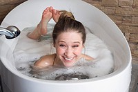 Young woman in bathtub, smiling, portrait