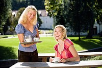Germany, Bavaria, Upper Bavaria, Young woman serving cup of coffee in beer garden