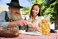 Germany, Bavaria, Upper Bavaria, Bavarian man and Asian woman in beer garden, Asian woman testing a spot of snuff