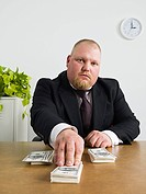 Businessman with stacks of money (thumbnail)
