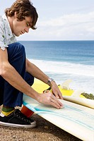 Surfer waxing board