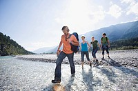 Germany, Bavaria, Tölzer Land, Young friends walking through river