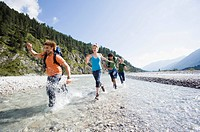 Germany, Bavaria, Tlzer Land, Young friends running through river (thumbnail)
