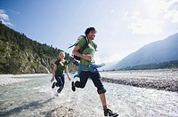 Germany, Bavaria, Tölzer Land, Young couple running through river