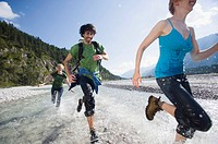 Germany, Bavaria, Tölzer Land, Young people running through river
