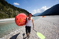 Germany, Bavaria, T&#246;lzer Land, Young man carrying a kayak and an oar, tent in background