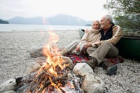 Germany, Bavaria, Walchensee, Senior couple sitting at campfire