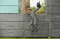 Germany, businessman jumping from wall