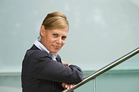 Germany, businesswoman leaning on railing