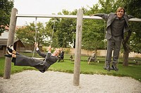 Germany, business people sitting on swings in playground