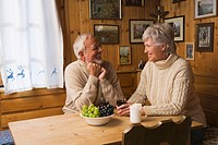 Senior couple sitting at table, smiling