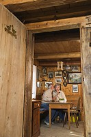 Senior couple sitting at table in Log Cabin