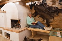 Senior woman in hunting lodge reading book