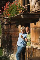 Austria, Karwendel, Senior couple leaning on log cabin, holding mugs
