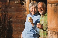 Austria, Karwendel, Senior couple leaning on log cabin, holding mugs, smiling, portrait