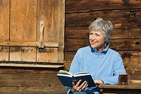 Austria, Senior woman reading book by log cabin, portrait