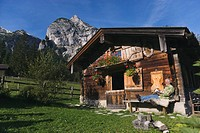 Austria, Karwendel, Senior man sitting in front of log cabin, reading a book
