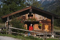 Austria, Karwendel, Senior woman standing in front of log cabin, smiling