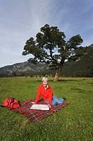 Austria, Karwendel, Senior woman sitting in meadow with map