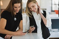 Two women in office using mobile phones, smiling