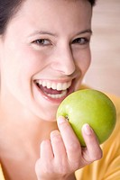 Young woman holding an apple, smiling, portrait