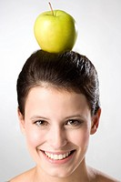 Young woman balancing apple on head, portrait