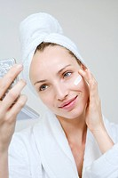 Young woman applying beauty cream, portrait (thumbnail)