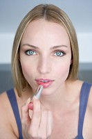 Young woman applying lipstick, portrai